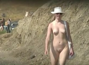 Naturist gal ambles on the beach just..
